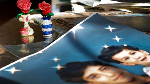 """In this  Dec. 10, 2014 file photo, Prison artwork created by Adnan Syed sits near family photos in the home of his mother, Shamim Syed, in Baltimore.  Syed, the subject of the popular podcast """"Serial"""" will be allowed to appeal his murder conviction, a Maryland court has ruled.  Adnan Syed, 34, was convicted in 2000 of strangling his ex-girlfriend, Hae Min Lee, the year prior, when both were high school students in suburban Baltimore."""