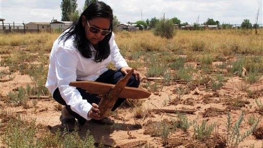 This July 9, 2014 file photo shows Navajo archaeologist Kim Mangum picking up a wooden cross at the Winslow Indian Cemetery. | Gail Sadler of Winslow spent about 1,200 hours going through death certificates to create an index that lists 542 people laid to rest at the cemetery tied to a former tuberculosis sanatorium. Sadler's next goal is to secure enough money for a granite memorial plaque bearing the cemetery's name.