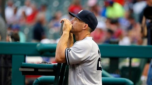 New York Yankees manager Joe Girardi stands in the dugout before the start of the first inning of a baseball game against the New York Yankees on Tuesday, April 26, 2016, in Arlington, Texas.