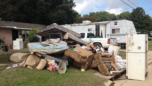A growing pile of debris sits outside the flood-ravaged home of Carolyn and James Smith in Denham Springs on Wednesday, Aug 17, 2016. Smith says she and four other adults will live for the time being in the travel trailer that one of her sons towed to the driveway after weekend flooding inundated the area.