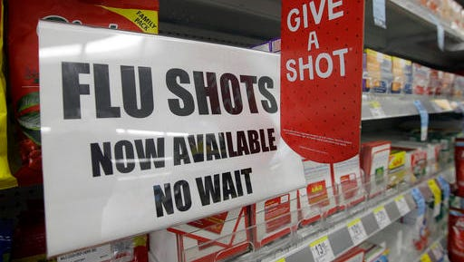 FILE - In this Sept. 16, 2014 file photo, a sign telling customers that they can get a flu shot in a Walgreen store is seen in Indianapolis. Kids may get more of a sting from flu vaccination this fall: Doctors are gearing up to give shots only, because U.S. health officials say the easy-to-use nasal spray version of the vaccine isn't working as well as a jab. Needle-phobic adults still have some less painful options. But FluMist, with its squirt into each nostril, was the only ouch-free alternative for children, and has accounted for about a third of pediatric flu vaccinations in recent years. (AP Photo/Darron Cummings, File)