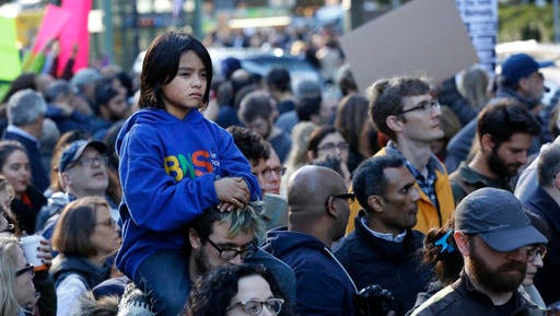 Nat Vandyke, 7, rides on his father's shoulders as they join a march of demonstrators protesting President-elect Donald Trump, Sunday, Nov. 13, 2016 in New York. Organizers said the protest was about speaking out against Trump's support of deportation and other measures. (AP Photo/Mark Lennihan)