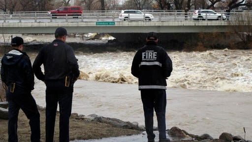 Sparks firefighters monitor the rising Truckee River, Sunday where it runs near the Grand Sierra hotel-casino along a line that divides the cities of Reno and Sparks, Nev. More than 1,000 homes have been evacuated due to overflowing streams and drainage ditches in the area, which remains under a flood warning through Tuesday. (AP Photo/Scott Sonner)
