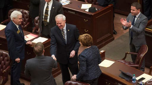 """FILE - In this Tuesday, Jan. 10, 2017, file photo, Arkansas Gov. Asa Hutchinson, center, greets legislators before his address to a joint session 91st General Assembly at the state Capitol in Little Rock, Ark. President-elect Donald Trump and congressional Republicans have pledged to cut federal taxes to boost the economy. But some GOP-controlled states have already adopted similar strategies, only to see growth falter and budget gaps widen. """"It does not take a Ph.D. in economics to know that we can't say yes to every spending need, and we should also not say yes to every tax-cut idea,"""" Hutchinson warned late last year. (AP Photo/Brian Chilson, File)"""