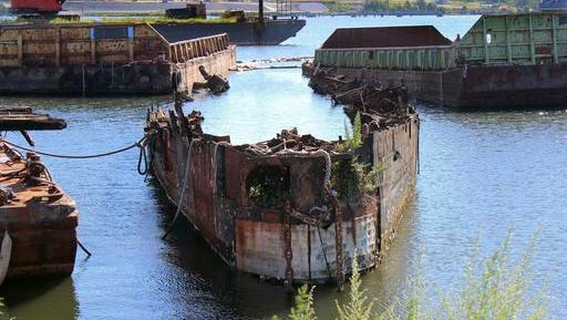 FILE - In this Aug. 22, 2016 file photo, rusting remnants of an old Russian submarine, used as a set for a Harrison Ford movie and as a floating museum until sinking during a 2007 nor'easter, sits rusting in a scrapyard in the Providence River in Providence, R.I. State environmental officials sued to have the sub and several other vessels removed from the river. A state superior court judge ordered Rhode Island Recycled Metals LLC in December to begin removing the vessels from the river. The permitting process is underway.