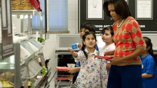 First lady Michelle Obama walks down the school lunch line with schoolchildren in the cafeteria at Parklawn Elementary School in Alexandria, Va., on Jan. 25, 2012.