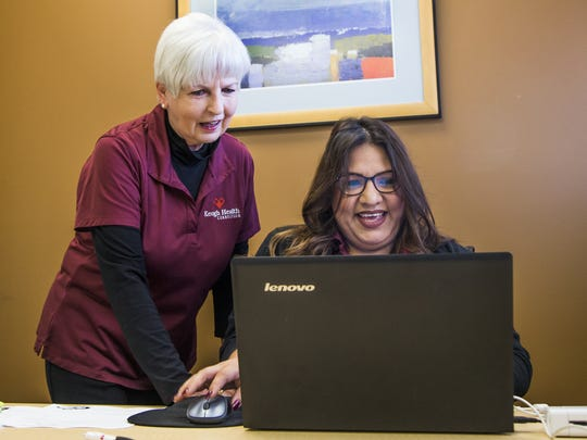 Saundra Johnson, executive director of Keogh Health Connection, (left) speaks with navigator Veronica Rivas as she processes information.