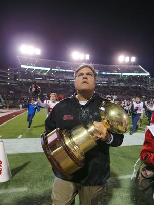 Ole Miss interim head coach Matt Luke takes the Egg Bowl trophy to the Ole Miss fans following the Rebels' 31-28 victory over Mississippi State Thursday in Starkville.