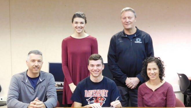 Olivet High School senior Colin Grady signs a National Letter of Intent to run track and field at NCAA Division II Davenport University. He is seated between his parents - Kevin Grady and Lauri Janousek. Standing are his sister, Aleena Janousek and Olivet Athletic Director Matt Seidl.