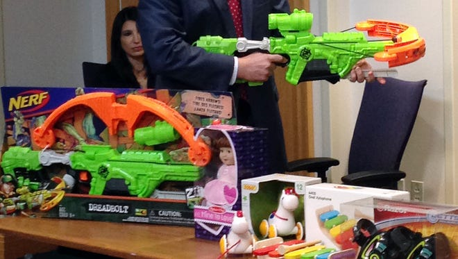 "James Swartz, director of World Against Toys Causing Harm, or W.A.T.C.H., displays Nerf's ""Zombie Strike"" crossbow during a news conference Tuesday, Nov. 14, 2017, in Boston, where the child safety group released its annual holiday list of the 10 most hazardous toys."