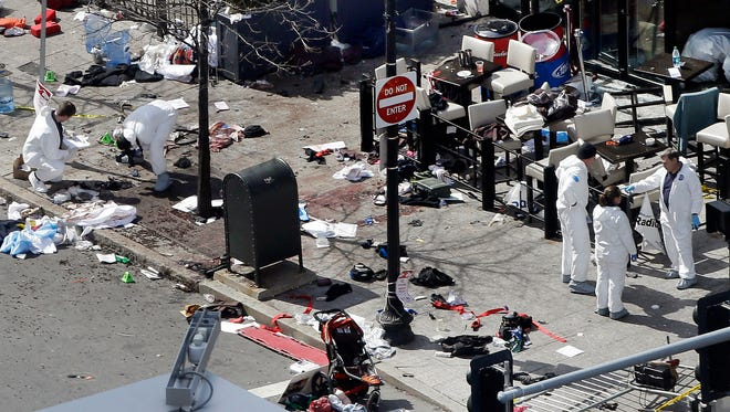 In this April 16, 2013 file photo, investigators examine the scene of the second bombing outside the Forum Restaurant on Boylston Street near the finish line of the 2013 Boston Marathon, a day after two blasts killed three and injured more than 260 people.