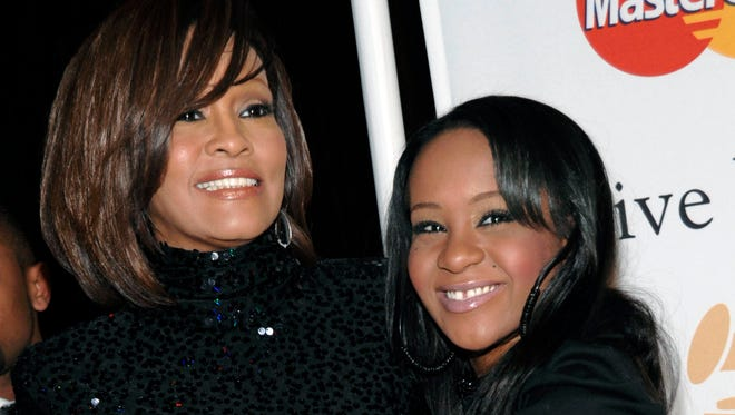 FILE - In this Feb. 12, 2011, file photo, singer Whitney Houston, left, and daughter Bobbi Kristina Brown arrive at an event in Beverly Hills, Calif. Bobbi Kristina, who dreamed of growing up to achieve fame like her mother, died in hospice care July 26, 2015, about six months after she was found face-down and unresponsive in a bathtub in her suburban Atlanta townhome. For Houston fans, the scene was grimly similar to the way her megastar mother had died three years earlier. (AP Photo/Dan Steinberg, File)