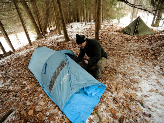 FILE - In this January 2015 photo, Mark LeGreve, board president of The Haven men's homeless shelter, shows his single-person tent that he used overnight to raise awareness for homelessness at Point Beach State Park in Two Rivers.