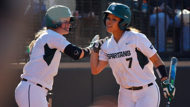 Michigan State's Shanin Thomas (7) is congratulated by Lea Foerster after scoring against Indiana Friday, April 15, 2016, in East Lansing, Mich. Michigan State won 6-2.