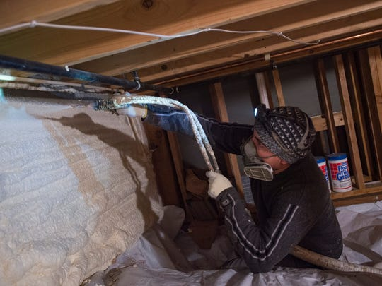 Chris Reyes of Efficiency Matters sprays foam in the lining of a crawl space in a Fort Collins home Wednesday, Dec. 21, 2016. The material provides a more energy-efficient layer to combat heating and cooling loss in the home.