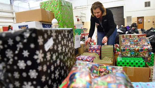 Volunteer Susan Pauly prepares gifts for distribution as part of the Share the Spirit program Dec. 10, 2015, at the St. Cloud Armory.
