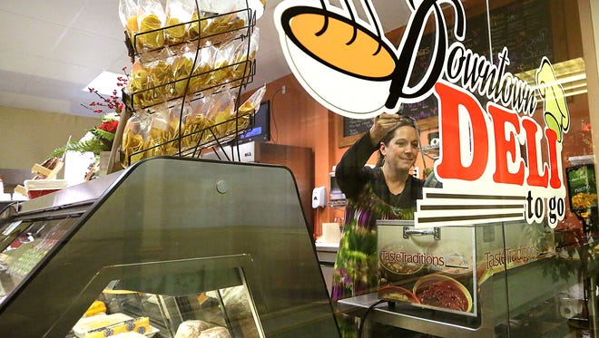 Downtown Deli to Go owner Kari Koenigs pours a bowl of soup on a recent day. Despite setbacks downtown, entrepreneurs keep opening businesses there. The deli opened Dec. 5.