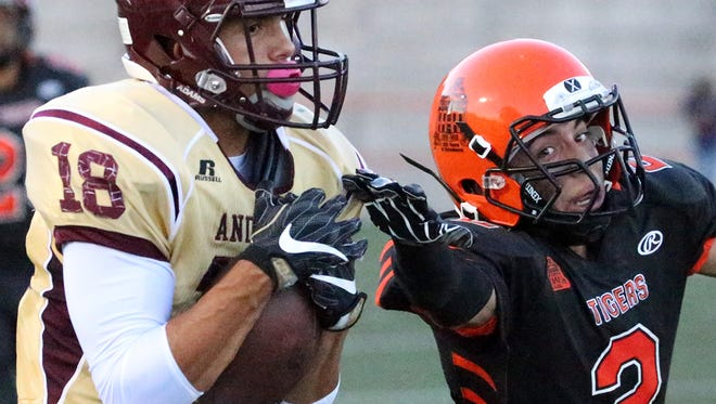Andress wide receiver Antonio Gomez grabs the long throw before running it in for a score despite the efforts of El Paso High's Luciano Carrillo, 2, Thursday night at El Paso High's Jones Stadium.