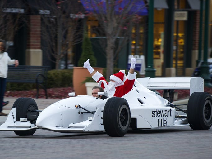 IndyCar Series driver Ed Carpenter was at the wheel of a two-seater race car as Santa Claus arrived in Carmel Saturday, November 16, 2013. Indianapolis Motor Speedway and the American Dairy Association of Indiana partnered with Clay Terrace shopping mall to deliver the iconic elf to the annual tree lighting event. Doug McSchooler / for The Star