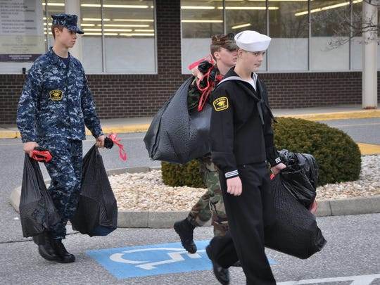 Sea Cadets carry bags of toys on Dec. 13 for Toys for Tots.