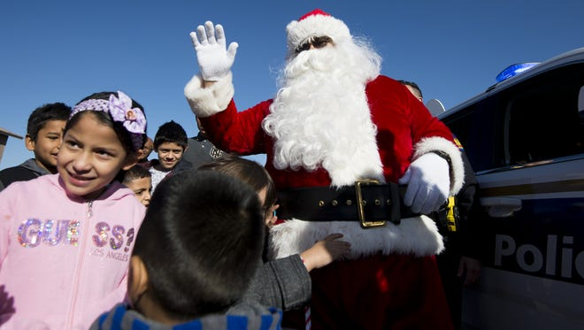 Santa Claus greets children during a holiday event at the Chicanos por la Causa community center in Phoenix on Dec. 17, 2016. CPLC and the Phoenix Police Department partnered to hand out toys to about 150 children in need at the event.