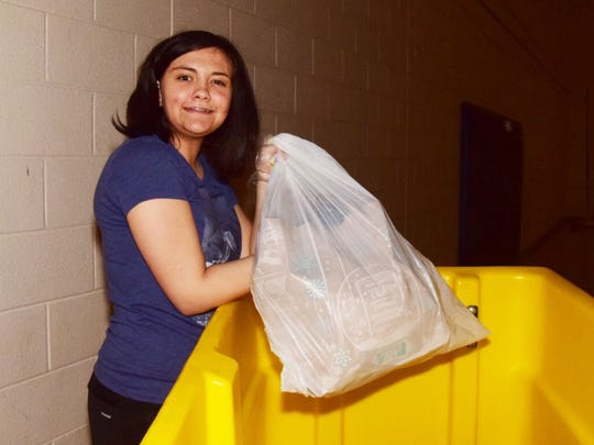 Cami James, 15, unloads bags filled with shoes ready for processing.