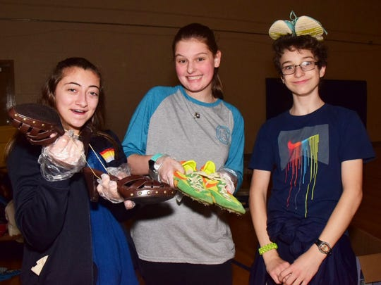 Friends Kelsey James, 14, Megan Rains, 16, and Jackson McNutt, 12, take a moment to get silly with shoes.