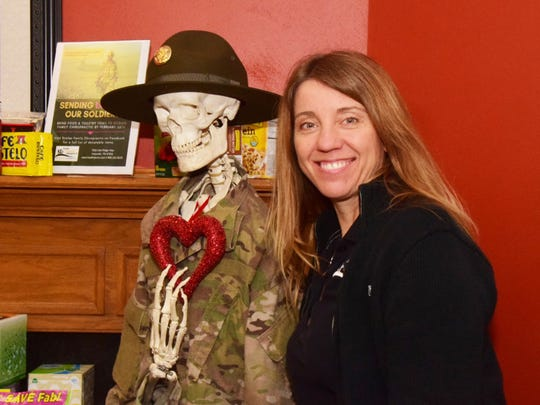 "Office manager Kelli Friedmann takes a pause with Rusty Bones dressed in a military uniform. ""He's the talk of the office,"" said Friedmann."