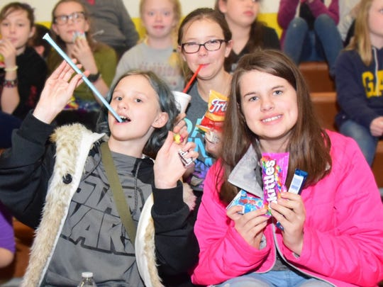 Cherish Young, 12, Emily O'Connor, 12, and Kennedy Shubert, 12, show off the goodies they bought with their Bucks.
