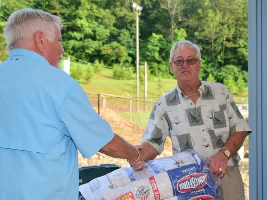 Lions Club member Roy Wayne congratulates Bill Slover, who won a grill and two bags of charcoal donated by Lowe's on Clinton Hwy.