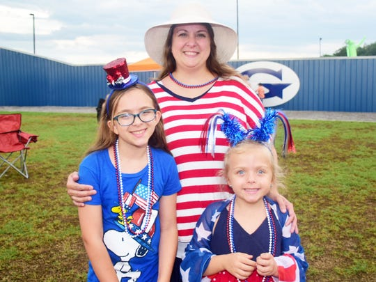 """Makayla Gardner, 11, Sarah Gardner, and Caroline Gardner, 6, brave the gloomy skies at the annual Grace American Celebration held at Grace Baptist Church Sunday, July 1. """"We come every year,"""" said mom Sarah Gardner."""" We always see familiar and friendly faces that we don't normally get to see during the year."""""""