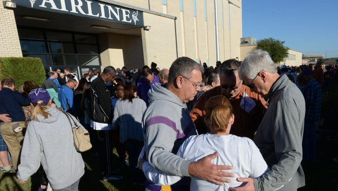 A group prays together Saturday morning in front of Airline High School.