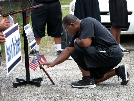 "The Rev. Malachi Walker kneels by a cross in honor of Ofc. Perry Renn as he and his Young Men Inc. Youth Ministry give ""High Honors"" to Officer Perry Renn Tuesday afternoon, July 8, 2014, near the scene where he lost his life in the line of duty at 34th and Forest Manor Ave."