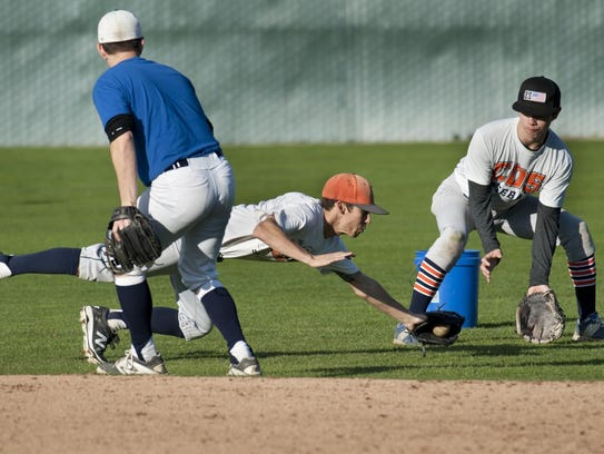 Jacob Trimble, center, grabs a hit ball during College