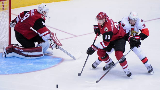 Arizona Coyotes defenseman Oliver Ekman-Larsson (23) steals the puck from Ottawa Senators center Mika Zibanejad (93) as goalie Anders Lindback (29) looks on in the first period at Gila River Arena. Mandatory Credit: