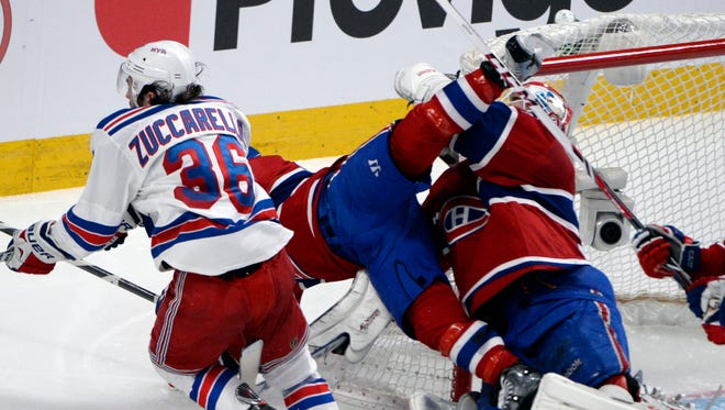 New York Rangers forward Mats Zuccarello (36) hits Montreal Canadiens forward Brian Gionta (21) into Montreal Canadiens goalie Dustin Tokarski (35) during the second period.