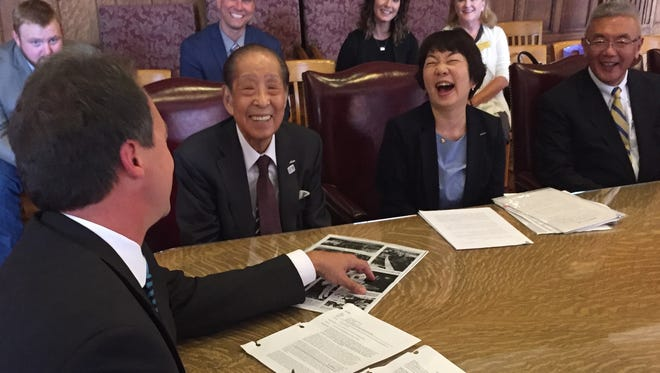 Gov. Steve Bullocks shares a laugh Monday with Nippon Flour Mills Co. CEP Hiroshi Sawada over a 1967 Tribune newspaper article that Sawada presented to show he was in Montana 50 years ago.