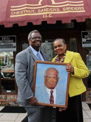 State Sen. Hank Sanders and his wife, Faya Toure, hold a portrait of the late J.L. Chestnut who was senior partner in Alabama's largest black law firm.