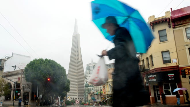A man passes the Transamerica building as rain pounds San Francisco's North Beach district on Thursday. A powerful storm churned through Northern California on Thursday, knocking out power to tens of thousands and delaying commuters while soaking the region with much-needed rain.