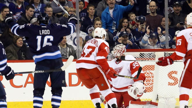 Jets left wing Andrew Ladd (16) celebrates his goal on Red Wings goalie Jimmy Howard (35) during the first period at MTS Centre Tuesday.