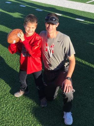 A.J. Cucksey poses with Maryville coach Derek Hunt, showing off the football the team autographed for him, after practice Tuesday, Nov. 29.