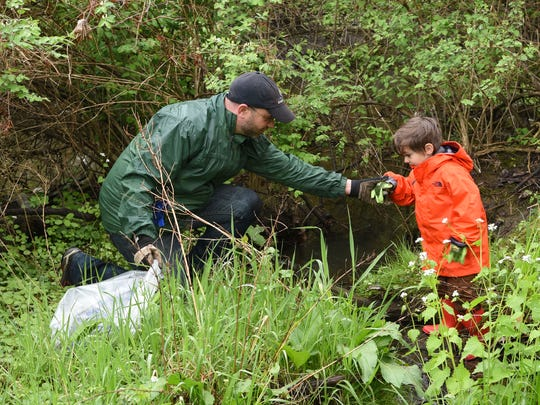Riverkeeper's water quality program manager, Dan Shapley and his son Ben help remove litter from the Casperkill Creek on the campus of Vassar College on Saturday during the 5th annual Riverkeeper Sweep.
