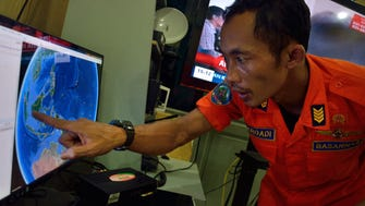 An official from Indonesia's national search and rescue agency in Medan, North Sumatra, points at his computer screen to the position where AirAsia flight QZ8501 went missing off the waters of Indonesia on  Saturday.