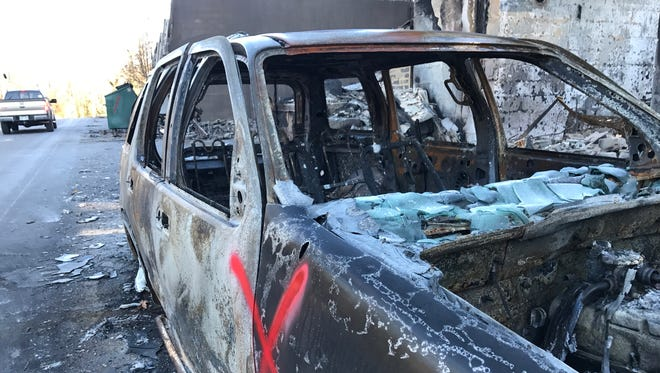 """The shell of a car, burned in wildfires earlier this week, sits Dec. 2, 2016, along the side of Cherokee Orchard Road in Gatlinburg, Tenn. The """"X"""" means emergency workers have checked the vehicle for fire victims."""