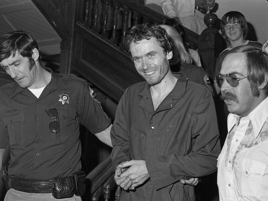 In this 1977 file photo, serial killer Ted Bundy, center, is escorted out of court at the Pitkin County courthouse, Aspen, Colo.