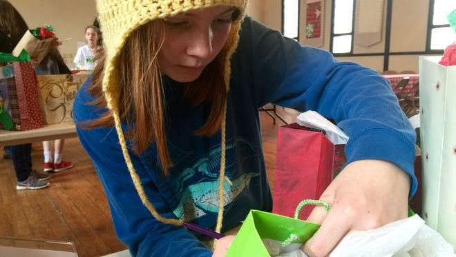 Elaine Boody, 12, carefully writes the name of a foster child on a present she wrapped Saturday.