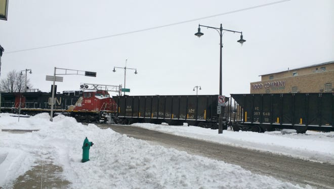 A train blocks the intersection of West College Avenue and Memorial Drive in Appleton after striking an unoccupied car that was on the tracks.