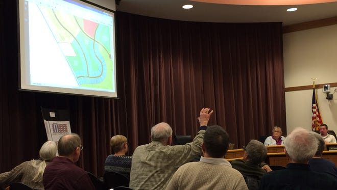 A resident raises his hand as the Coralville Planning and Zoning Commission examines a preliminary plan for a housing development that could be built south of Liberty High School.