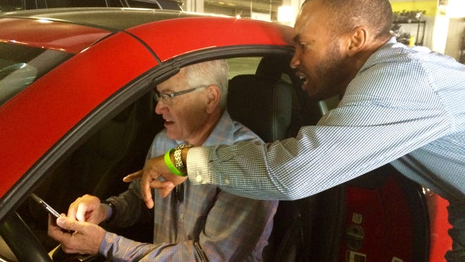 Bob Keller, a visitor from St. Louis, is assisted by Ricardo Love, general manager for Hertz operations at Southwest Florida International Airport. Keller was having difficulty connecting his phone to the car's Bluetooth system.