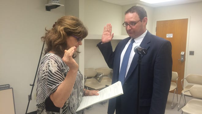 Jon Emaus dedicates himself to the city of Brighton Thursday. Acting City Clerk Pam Stewart administers the oath of office.